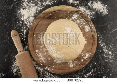Freshly Prepared Dough On A Wooden Board. Rolling Pin And Flour On Table. Top View.