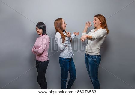 Two girls talking blonde European appearance and ignore the third girl on a gray background, resentm