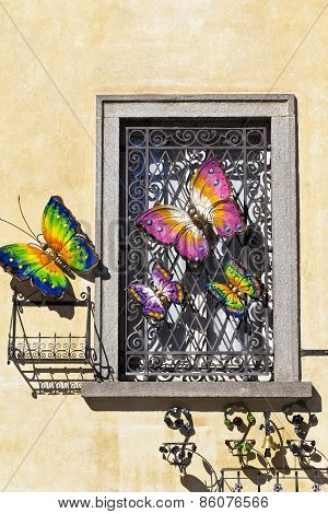 Rustic old window with iron butterflies on bright pastel colored stone wall