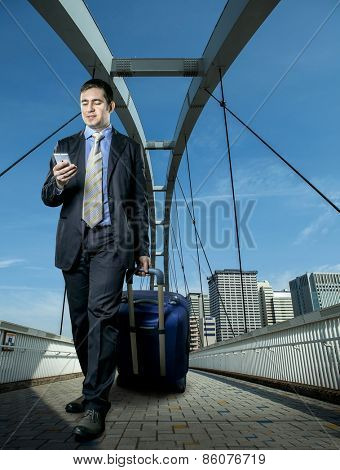 Man with baggage speaking by phone on the bridge