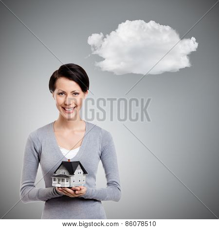 Young woman hands small toy house in front of herself, isolated on grey background with cloud