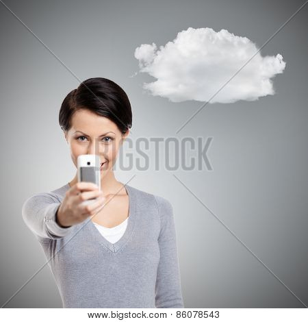 Pretty woman making a photo with mobile phone, isolated on grey background with cloud