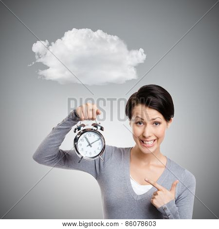 Sleeping pretty woman holds an alarm clock, isolated on grey background