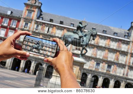 a tourist taking a picture of La Plaza Mayor in Madrid, Spain
