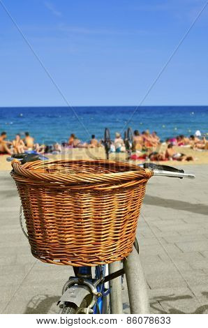 closeup of a bicycle with a wicker basket parked in the seafront with blurred people on the beach in the background