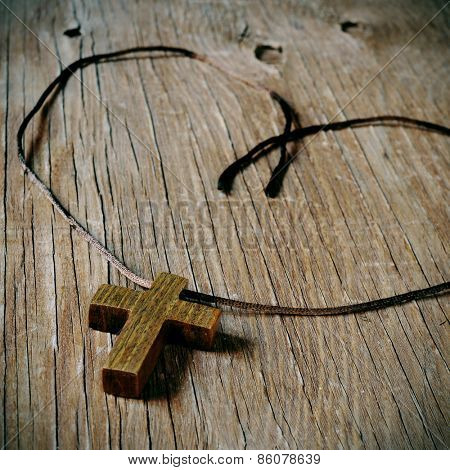 a simple wooden Christian cross on a rustic wooden surface