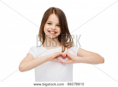 friendship, t-shirt design and happy people concept - smiling little girl in white blank t-shirts showing heart with hands