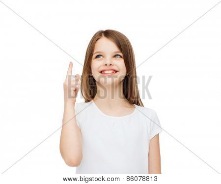 advertising and t-shirt design concept - smiling little girl in white blank t-shirt over white background pointing finger up