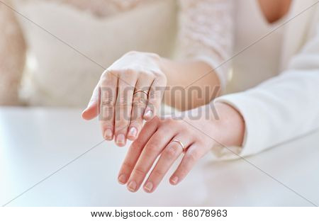 people, homosexuality, same-sex marriage and love concept - close up of happy lesbian couple hands showing wedding rings on