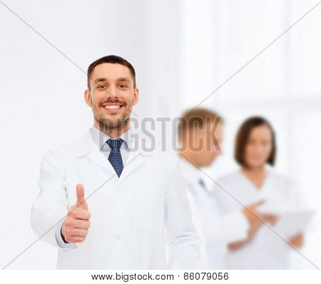 healthcare, profession and medicine concept - smiling male doctor showing thumbs up over white background