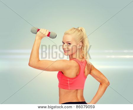 fitness, sport and diet concept - young sporty woman with light dumbbell