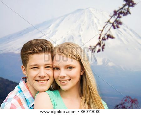 people, vacation, love and travel concept - smiling couple hugging over japan mountains background