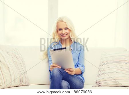 home, technology and internet concept - smiling woman sitting on the couch with tablet pc computer at home