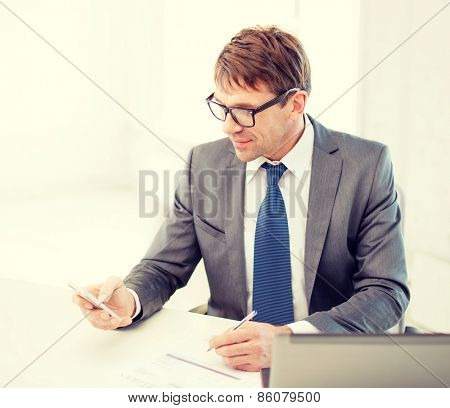 technology, business, internet and office concept - handsome businessman working with laptop computer and smartphone