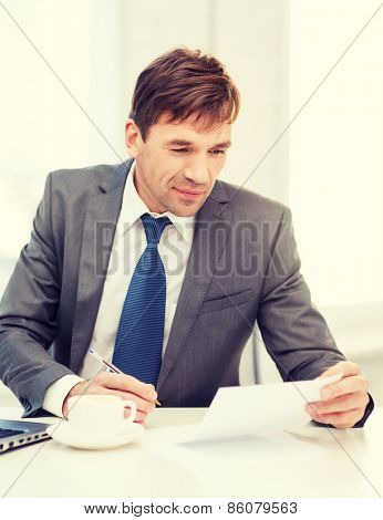 technology, business and office concept - handsome businessman working with laptop computer and documents