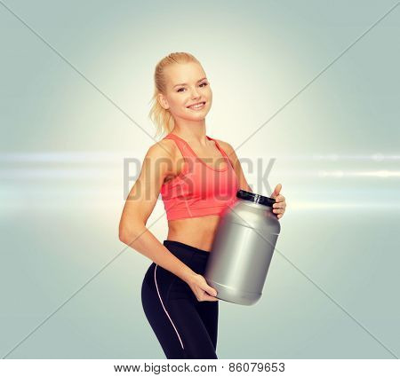 fitness and diet concept - smiling sporty woman with jar of protein