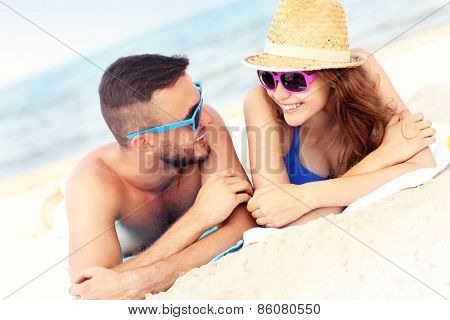 A picture of a happy couple lying on the beach and talking