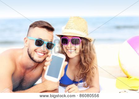 A picture of a happy couple showing smartphone screen at the beach