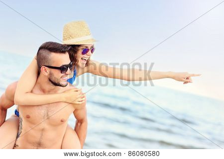 A picture of a happy couple pointing at something at the beach