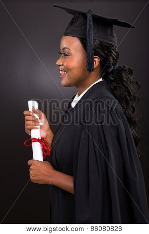 side view of happy young african female graduate on black background