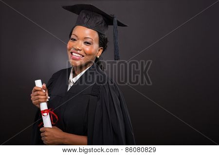 studio portrait of african college graduate on black background