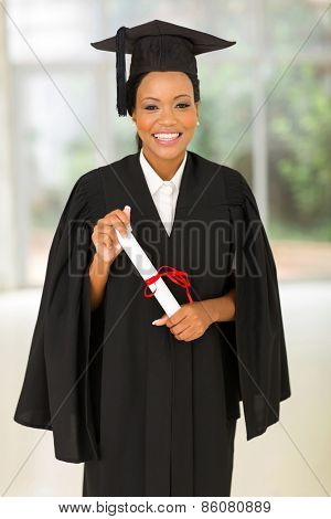attractive young black college graduate holding certificate indoors