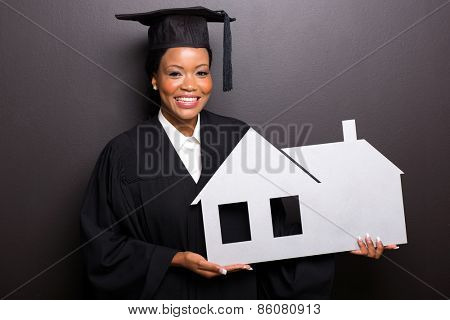 african american graduate holding home symbol isolated on black background