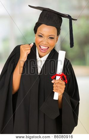 portrait of female graduate holding diploma in college hall