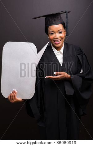 cheerful african female graduate with blank text bubble on black background