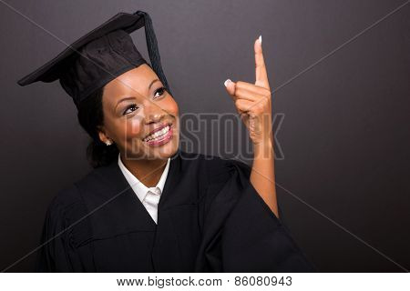 cheerful young african american graduate pointing up on black background