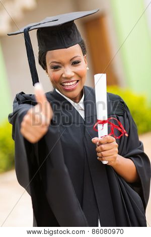african american female graduate thumb up outside college building