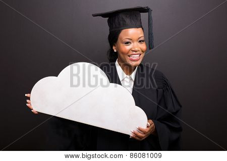 beautiful african college graduate holding cloud shape on black background