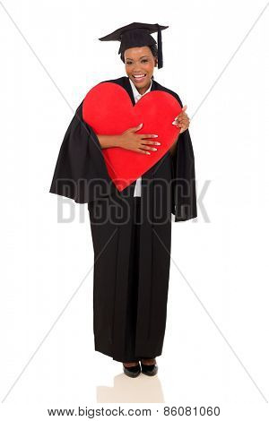 pretty african university graduate holding red heart isolated on white