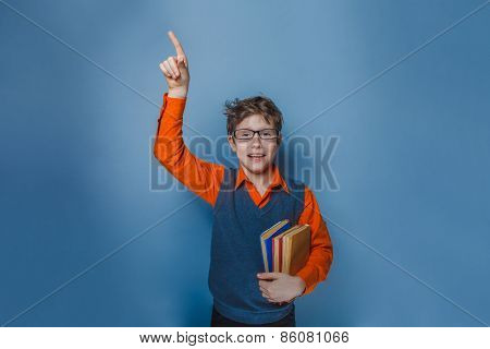 European-looking  boy of  ten  years  in glasses  thumbs up, the idea of the book on a blue backgrou