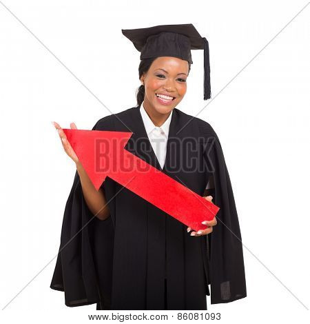 pretty african american college graduate holding red arrow on white background