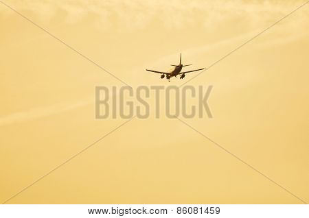 Airliner approaching airport for landing at sunset