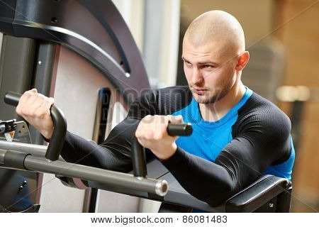 bodybuilder man doing excercises with weight training equipment on sport gym club
