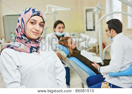 A portrait of a iranian muslim female dental assistant or doctor smiling the dentist working in the background