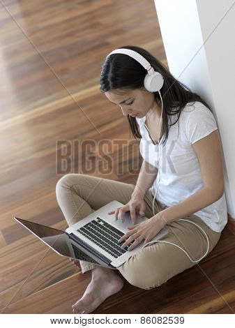 beautiful young woman relax and work on laptop computer modern  home office while listening musin on white headphones