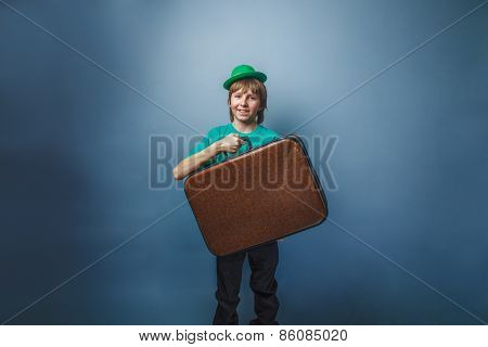 European-looking boy of ten years in a hat holding a suitcase in hand, itinerary on a blue backgroun