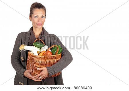Beautiful woman coming from the market with a basket full of vegetables