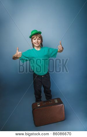 European-looking boy of  ten years in a hat holding a suitcase in hand, itinerary on a blue backgrou
