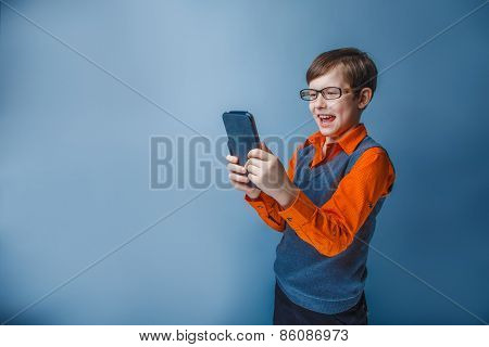 European-looking  boy of ten years in  glasses holding tablet in hand, plays, pleasure on a blue bac