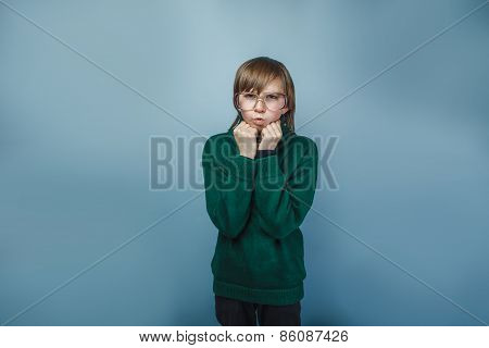 teenager boy with glasses lips blowing antics emotions fists in the face on a blue background