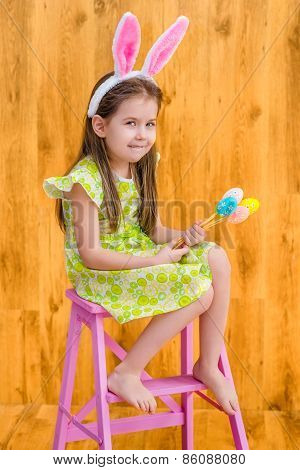 Barefooted little girl wearing pink white rabbit or bunny ears and holding bunch of colorful eggs
