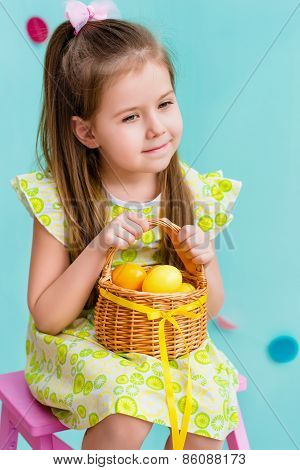 Thoughtful little girl with long blond hair holding wicker basket with yellow eggs