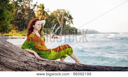 Beautiful Woman In Indian Bright Dress Is Sitting On The Snag On The Tropical Coastline Background