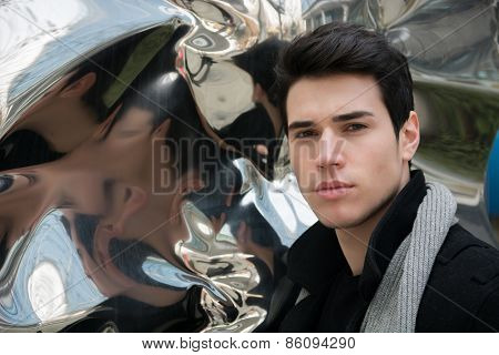 Handsome Young Man Next To Deforming Mirror