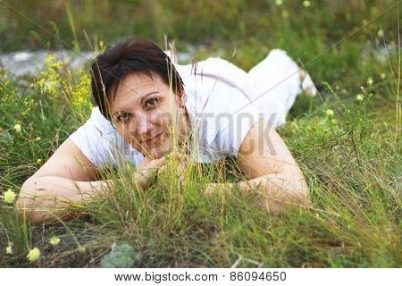 Woman Laying In The Grass On The Meadow