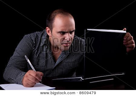 Surprised Businessman Looking To Computer And Taking Notes, Isolated On Black Background. Studio Sho